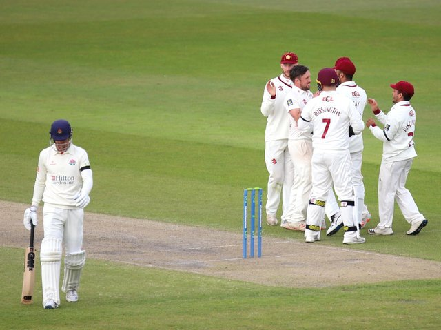 Simon Kerrigan is congratulated by his Northants team-mates after taking one of his three wickets against Lancashire (Pictures: Peter Short)